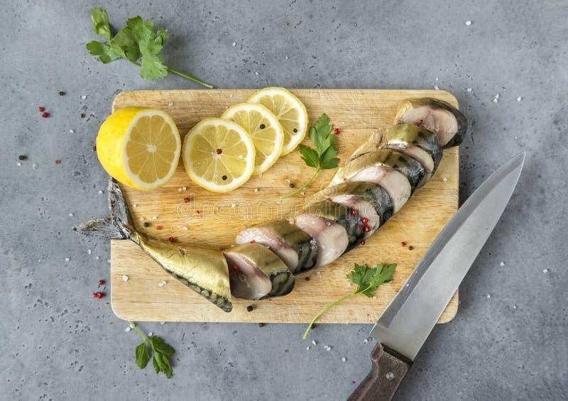 切的熏制的鲭鱼用香料和柠檬在一块砧板在灰色背景,顶视图 免版税库存照片