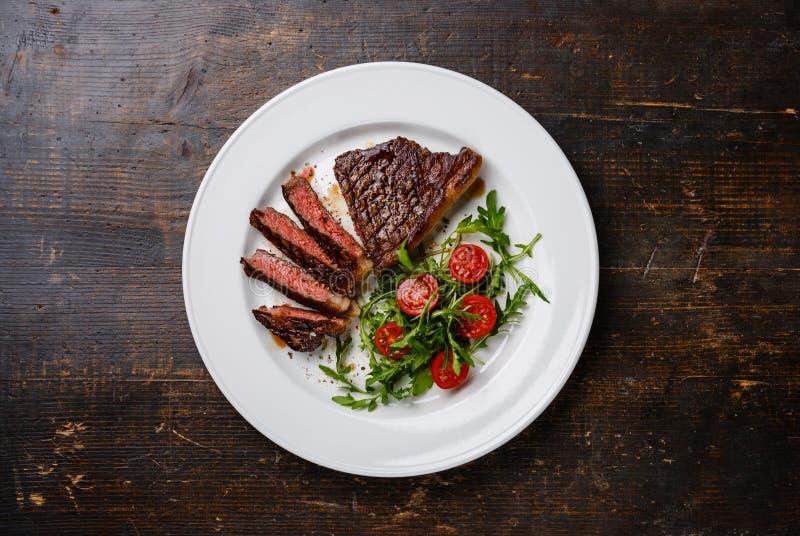 切的牛排Striploin和沙拉用蕃茄和芝麻菜 免版税图库摄影