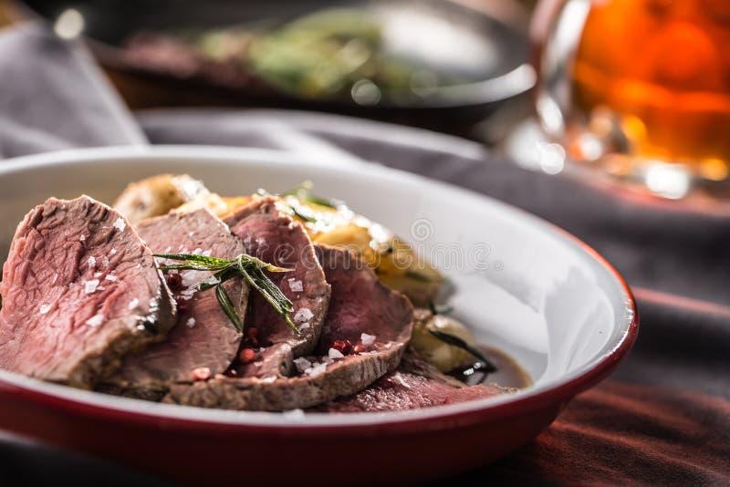 切的牛里脊肉烤了牛排土豆迷迭香和桶装啤酒 库存图片