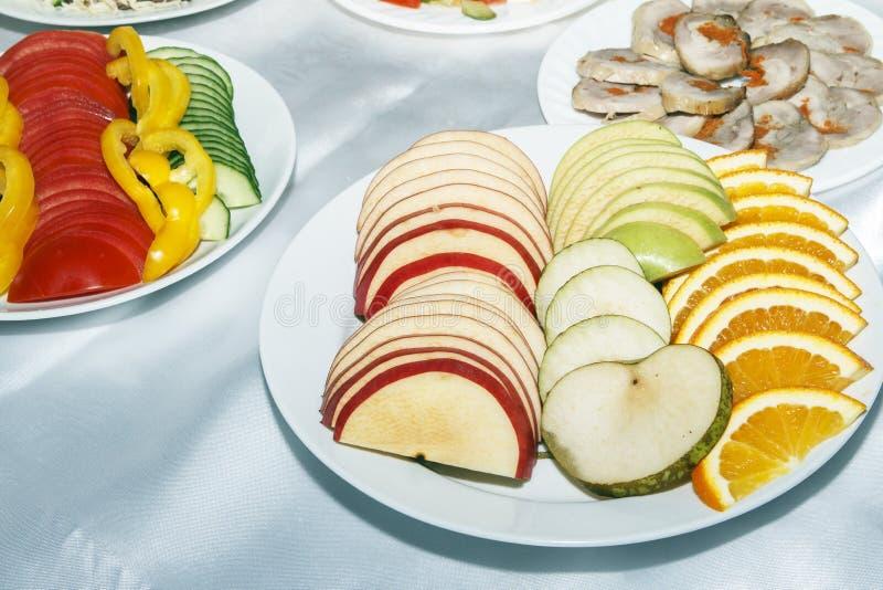 切的红色和绿色苹果和桔子在白色板材 招待会客人的新鲜的快餐在欢乐桌上 复制空间 免版税库存图片