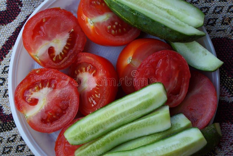 切的红色蕃茄和绿色黄瓜在一块白色塑料板材 库存图片
