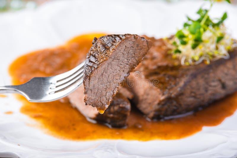切的罕见的烤牛排Ribeye用在白色板材的调味汁 选择聚焦 免版税库存图片