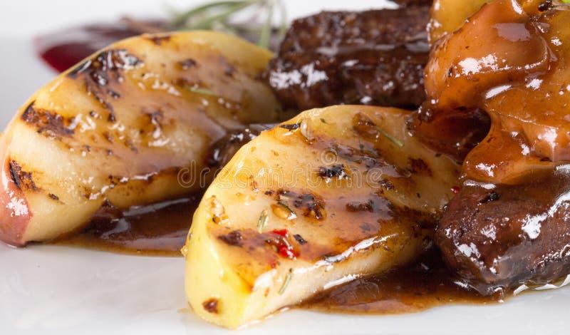 切的肉用烤土豆用焦糖的调味汁 库存图片