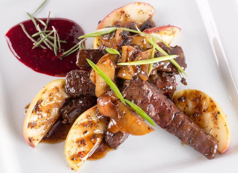 切的肉用烤土豆用焦糖的调味汁 免版税库存图片