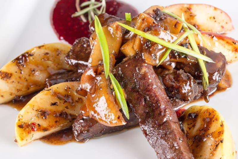 切的肉用烤土豆用焦糖的调味汁 库存照片