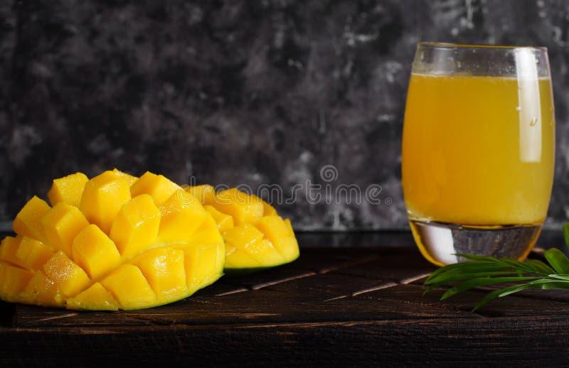 切的芒果和汁液在一块玻璃在一个木板有黑暗的背景 免版税库存图片