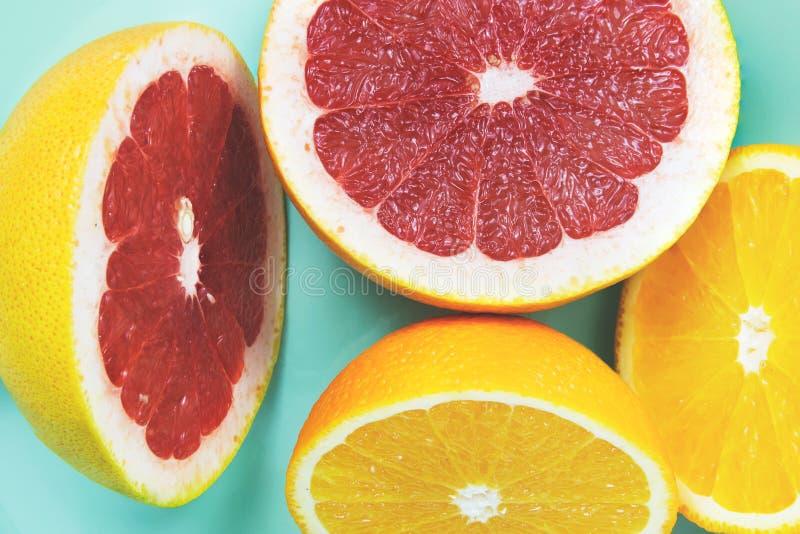 切的葡萄柚用在绿松石背景的桔子 库存照片