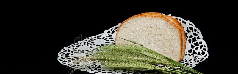 切的长的面包,装饰用在黑背景的麦子钉 在黑背景的麦子钉 概念:收获 免版税库存照片