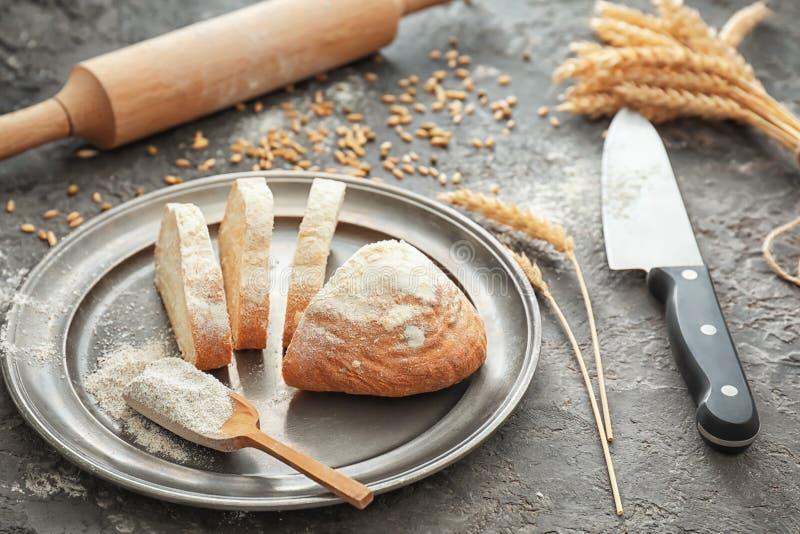 切的面包和瓢用小麦面粉在板材 免版税库存图片