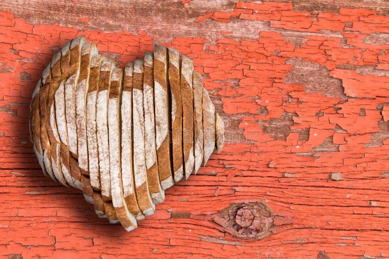 切的面包大面包塑造了作为在老表面的心脏 免版税图库摄影