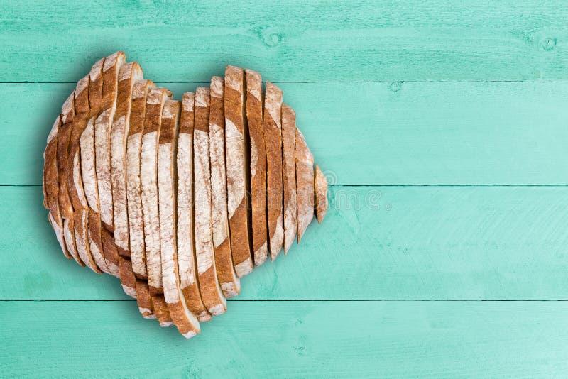 切的面包大面包塑造了作为在绿色木头的心脏 免版税库存照片