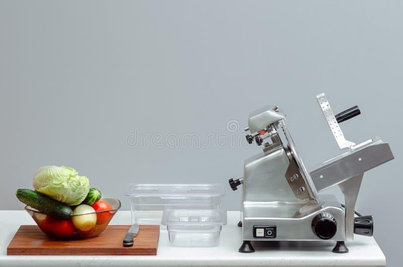 切的食物存贮的切片机在与菜的桌上和军用餐具 免版税库存照片