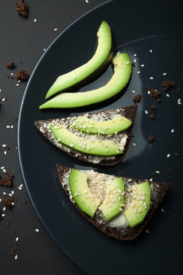 切的鲕梨用在黑面包的芝麻用乳酪 饮食早餐和饭食 图库摄影
