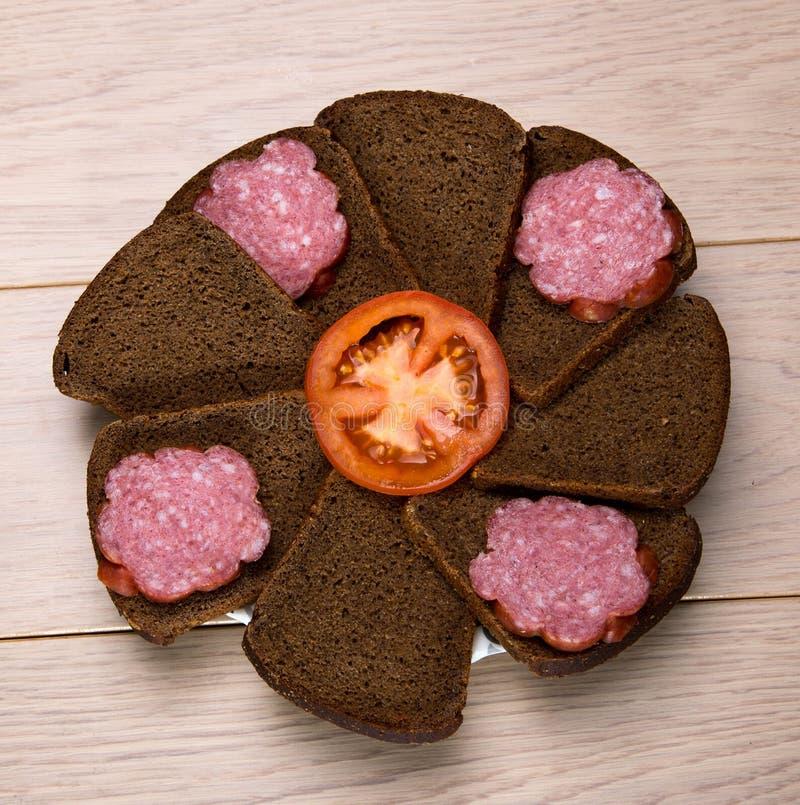 切的黑面包和香肠板材在木桌上 库存图片