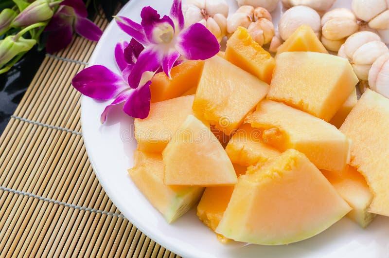 切的sunlady瓜和mangostine在白色板材 免版税库存图片