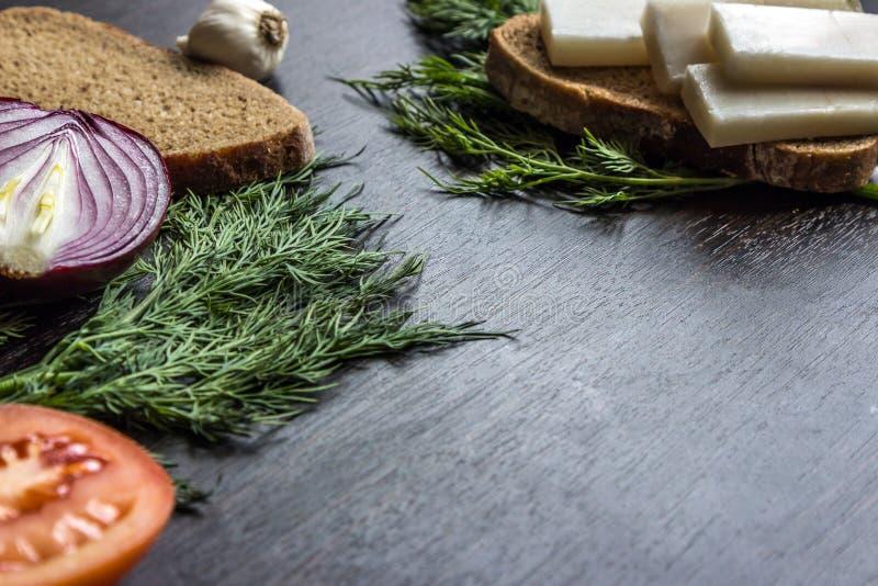 切红洋葱、蕃茄、莳萝、猪油salo和大蒜在木桌上 小的景深 免版税库存照片
