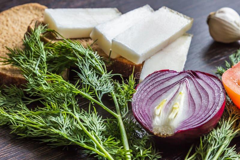 切红洋葱、蕃茄、莳萝、猪油salo和大蒜在木桌上 库存照片
