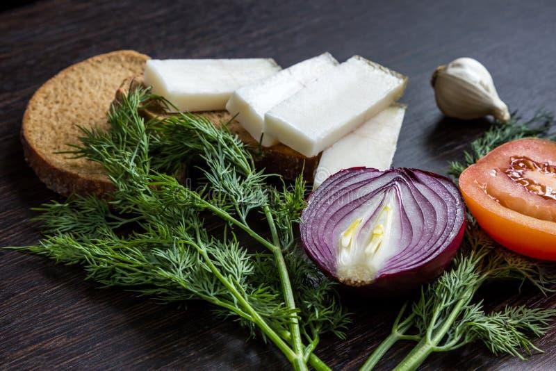 切红洋葱、蕃茄、莳萝、猪油salo和大蒜在木桌上 图库摄影