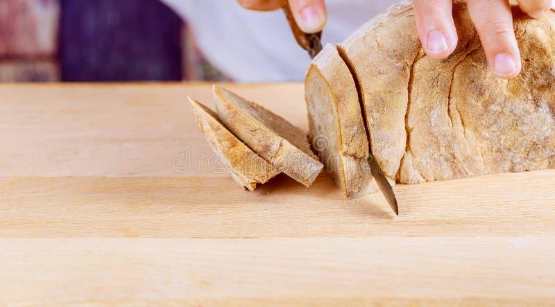 切自创全麦和五谷面包用刀子面包,切片大面包在木板背景 免版税库存照片