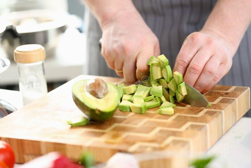 切节食的热带水果鲕梨的厨师手 免版税库存照片