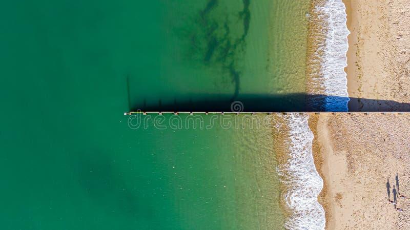 划分有碰撞的波浪的groyne防堤的一张鸟瞰图庄严cystal清楚的绿色水海在一晴朗含沙 免版税库存图片