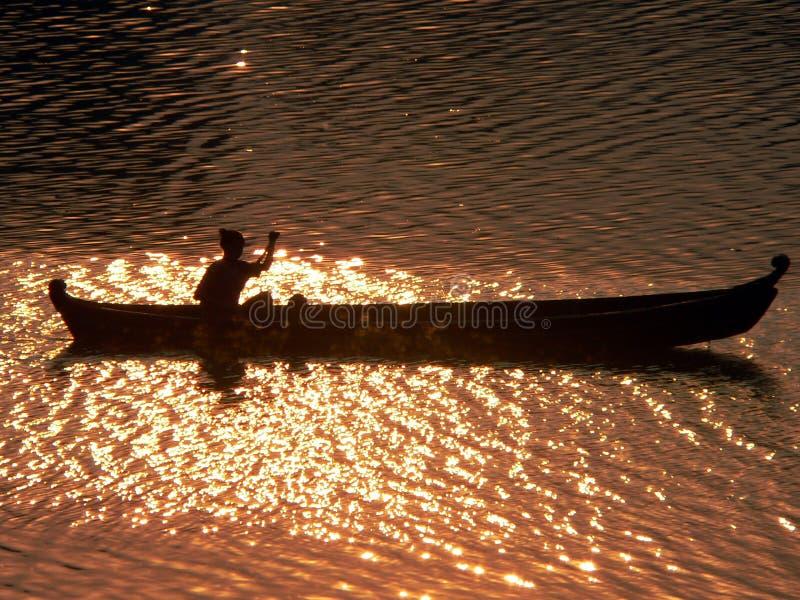 划独木舟的人irrawaddy河日落 图库摄影