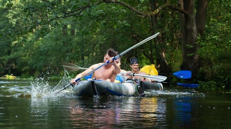 划皮船和乘独木舟在密林河 库存图片