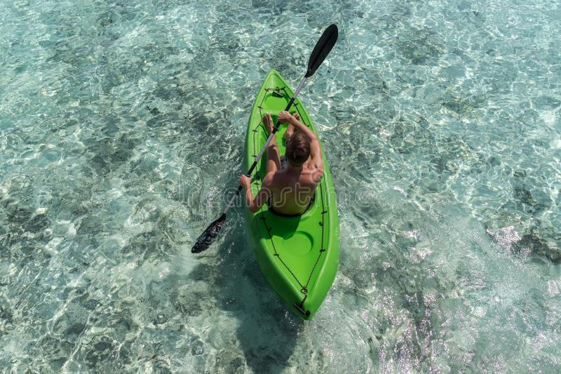 划皮船在一个热带海岛上的年轻愉快的人在马尔代夫 清楚的大海 免版税库存图片
