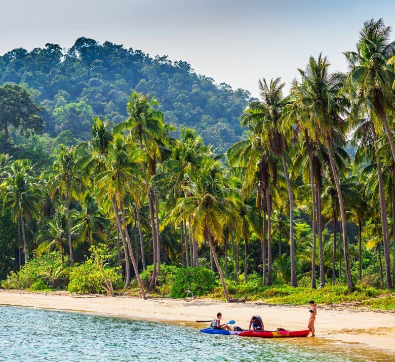 划皮船在与棕榈树的晴朗的热带海滩 免版税库存图片