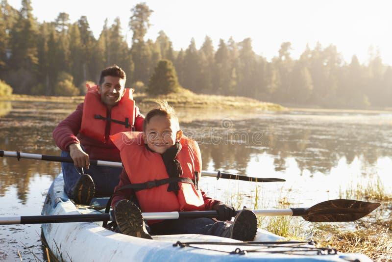 划皮船在农村湖,关闭的父亲和儿子  库存图片