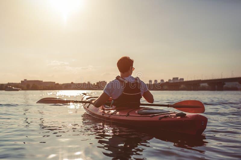 划皮船在日落的人 免版税库存照片