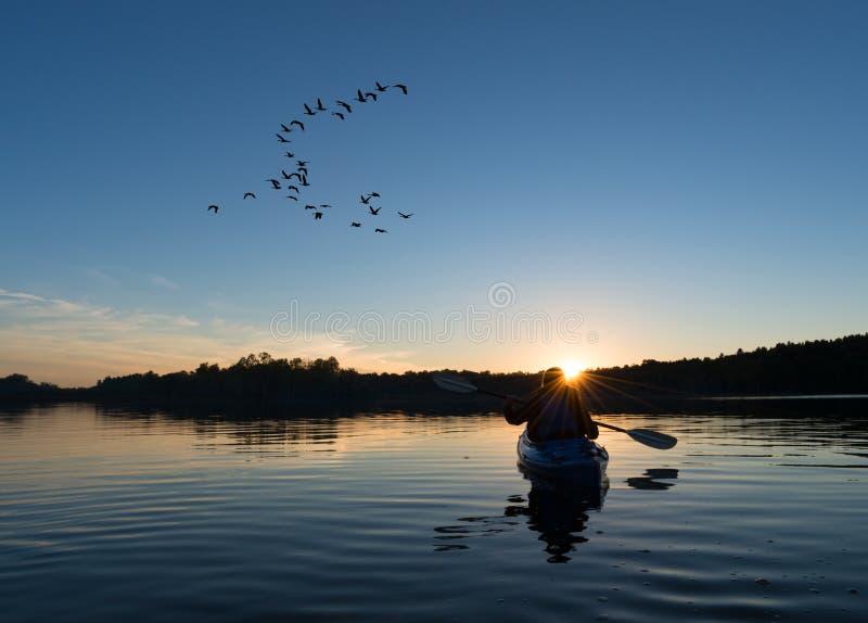 划皮船在日落的妇女 免版税库存图片