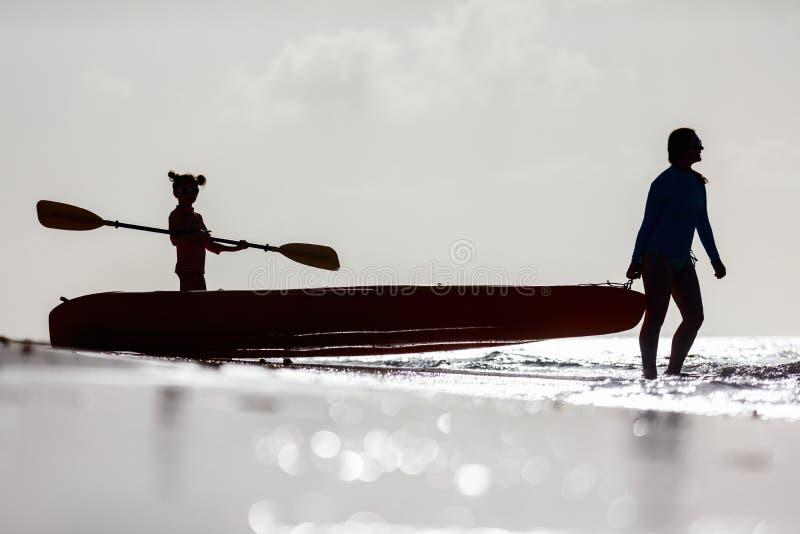 划皮船在日落的家庭 免版税库存图片