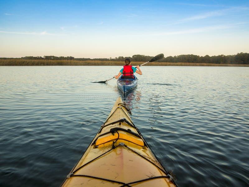 划皮船在日落的海 免版税库存图片