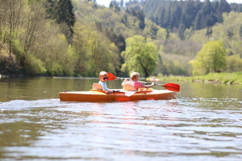 划皮船在河的孩子 库存图片