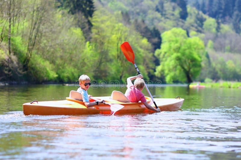 划皮船在河的孩子 免版税库存照片