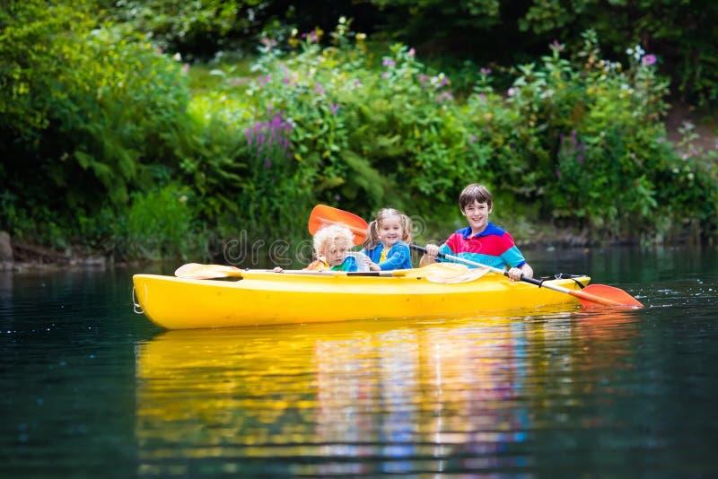 划皮船在河的孩子 免版税库存图片