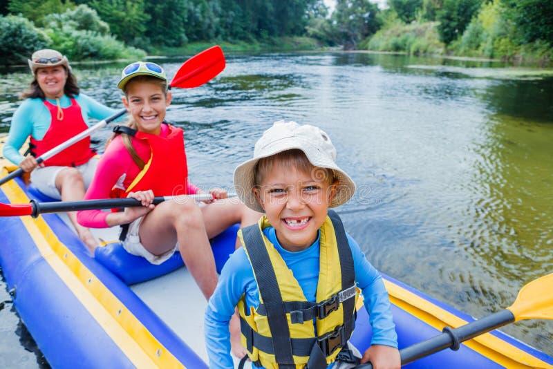 划皮船在河的家庭 库存图片