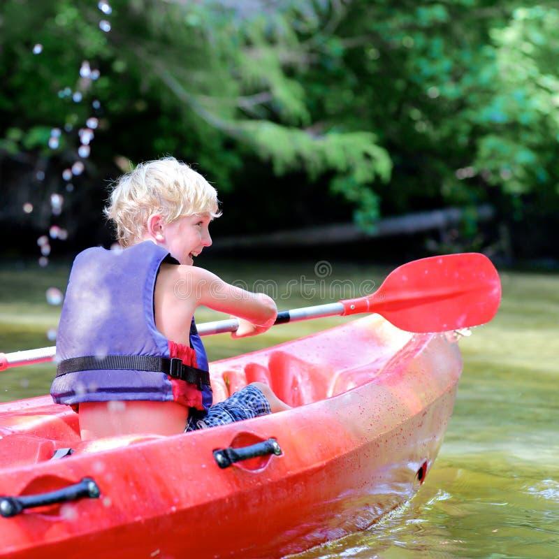 划皮船在河的活跃愉快的男孩 库存图片