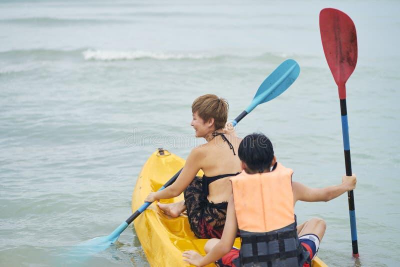 划皮船在海的愉快的母亲&儿子背面图  免版税库存照片