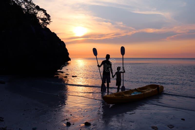 划皮船在海滩的人和女儿 免版税库存图片