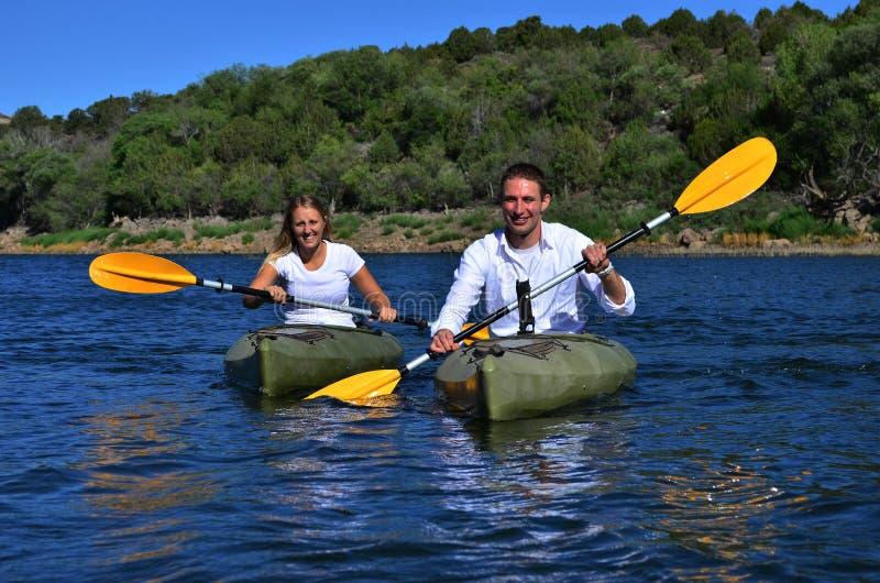 划皮船在湖的夫妇 免版税库存图片