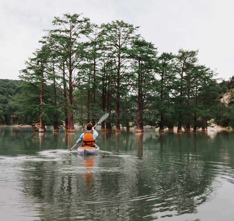 划皮船在湖的年轻人 图库摄影
