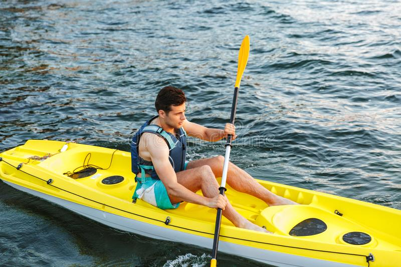 划皮船在湖的年轻人 库存照片
