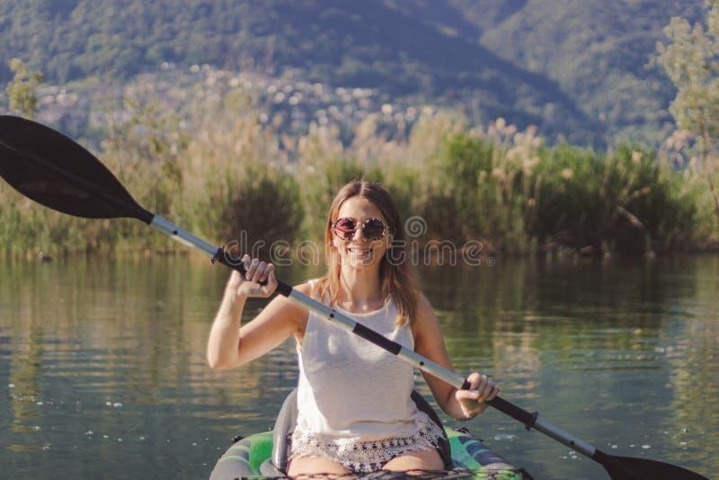 划皮船在湖的年轻女人 库存照片