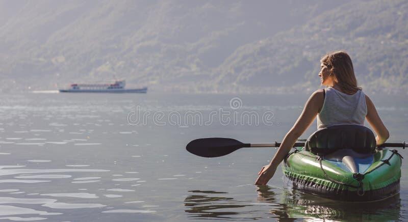 划皮船在湖的年轻女人 库存图片
