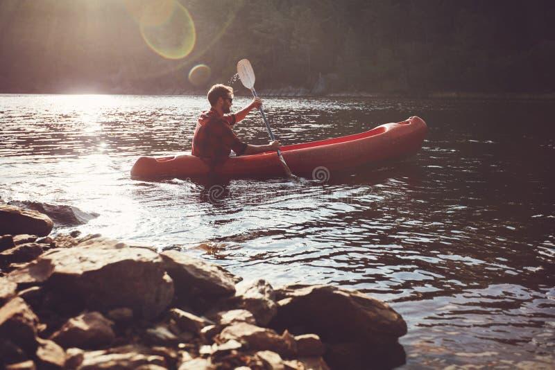 划皮船在湖的年轻人 库存图片