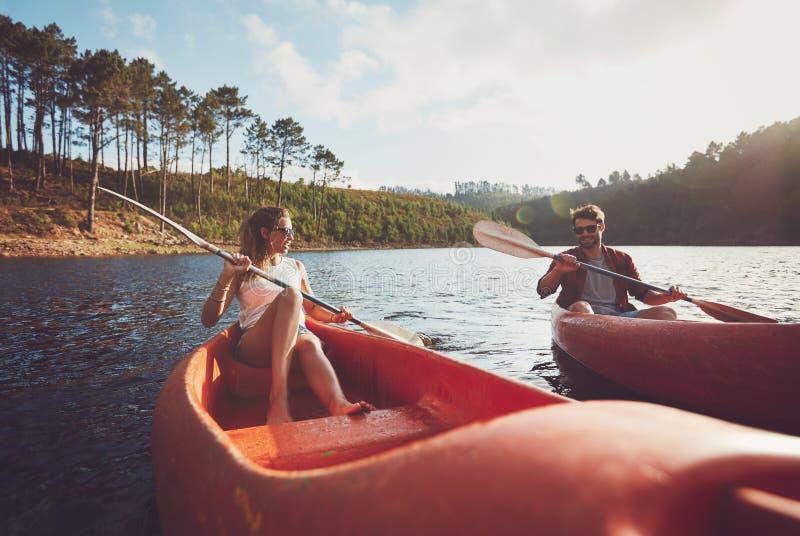 划皮船在湖的年轻夫妇 库存图片