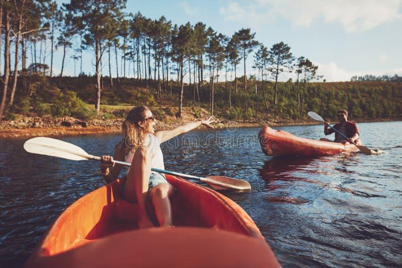 划皮船在湖的年轻夫妇 库存照片