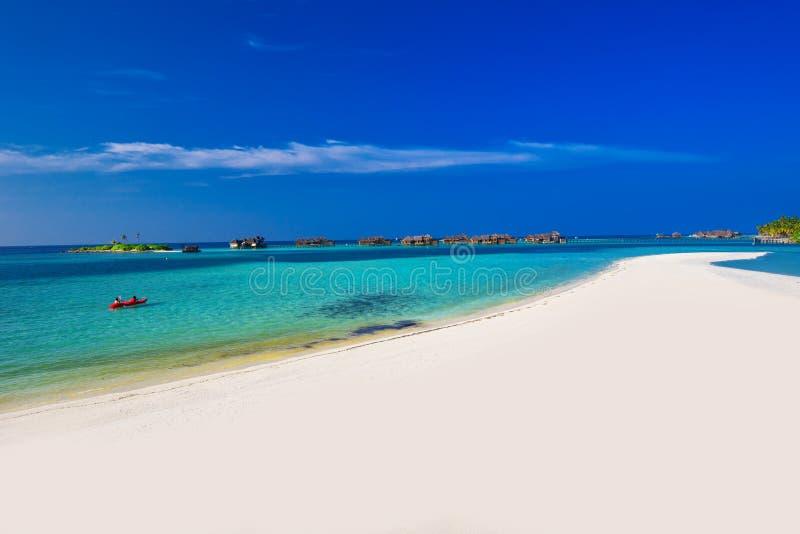 划皮船在热带海岛,马尔代夫上的绿色盐水湖的人们 库存图片